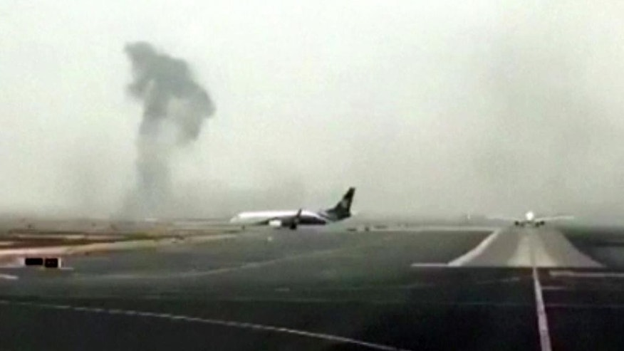 FILE- In this Wednesday, Aug. 3, 2016 file photo made from video shows smoke rising after an Emirates flight crash landed at Dubai International Airport. A preliminary report into last month's Emirates airliner crash landing in Dubai has found that the pilot attempted to abort the landing after an initial touchdown and that the plane ultimately hit the runway as its landing gear was retracting. (Hayen Ayari via AP, file)