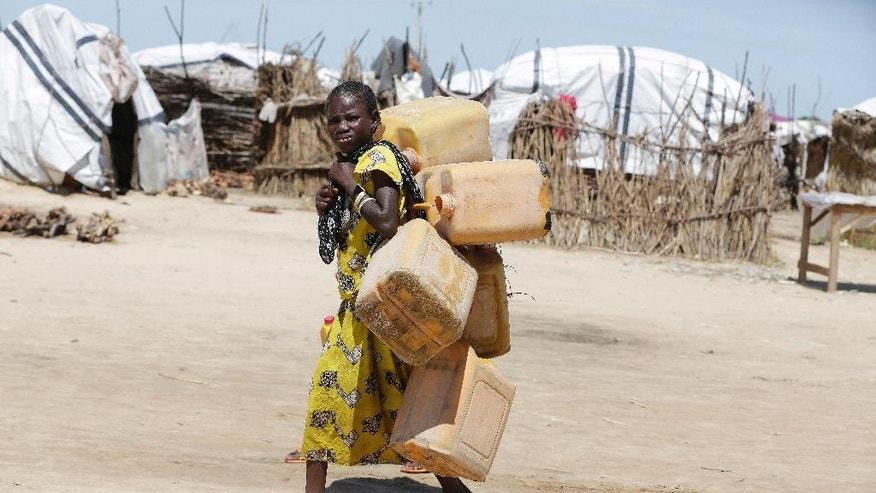 In this photo taken Sunday Aug. 28, 2016 a girl displaced by Islamist Extremists carries empty plastic containers at a camp Maiduguri, Nigeria. Excited and fear-filled refugees from Boko Haram piled onto buses with pathetic bundles of belongings, returning after two years to homes that have been torched, wells and crops destroyed, livestock looted and fields that may not be safe from the Islamic insurgents. (AP Photo/Sunday Alamba)