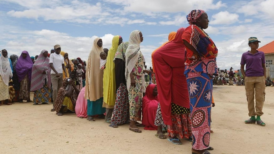 In this photo taken Saturday Aug. 27, 2016, women displaced by Islamist Extremists wait for food at Bakassi camp in Maiduguri, Nigeria. Excited and fear-filled refugees from Boko Haram piled onto buses with pathetic bundles of belongings, returning after two years to homes that have been torched, wells and crops destroyed, livestock looted and fields that may not be safe from the Islamic insurgents. (AP Photo/Sunday Alamba)