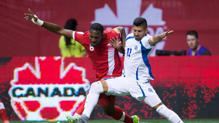 Canada's Doneil Henry, left, and El Salvador's Nelson Bonilla vie for the ball during the first half of a CONCACAF World Cup soccer qualifying match Tuesday, Sept. 6, 2016, in Vancouver, British Columbia. (Darryl Dyck/The Canadian Press via AP)