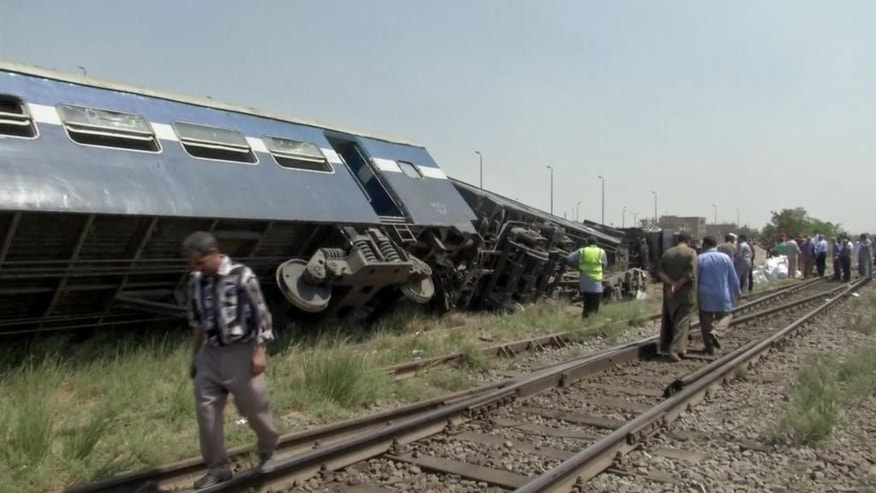 In this frame grab taken from AP video, rescue workers and onlookers gather at the site of a train derailment in Al-Ayat, about 50 kilometers (31 miles) south of Cairo, Egypt, Wednesday, Sept. 7, 2016. The train went off the tracks at least killing five people, according to the Health Ministry. The accident came during one of the busiest travel times of the year, when millions of Egyptians leave Cairo and other big cities to head to their hometowns and villages for Eid al-Adha, a major Muslim holiday that begins on Monday. (AP Photo/Mohamed Wagdy)