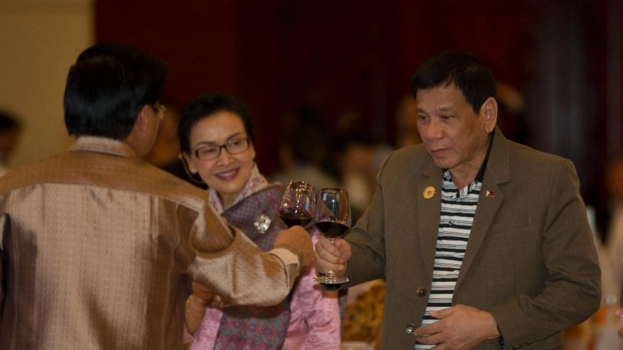 Philippine's President Rodrigo Duterte, right, toasts a drink with Laos Prime Minister Thongloun Sisoulith during Association of Southeast Asian Nations (ASEAN) summit welcome dinner in Vientiane, Laos, Tuesday, Sept. 6, 2016. (AP Photo/Gemunu Amarasinghe)