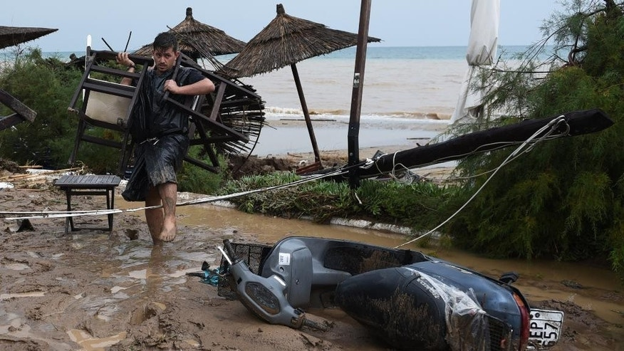 A man carries chairs while walking through the mud in Agia Triada village about 20 kilometers from the city of Thessaloniki, northern Greece, after heavy overnight rain on Wednesday, Sept. 7, 2916. Greek authorities said three people are dead and one is missing after the floods, which damaged homes and businesses in the southern Peloponnese region. AP Photo/Giannis Papanikos)