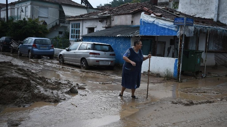 An elderly woman walks in the mud on a street of Agia Triada village about 20 kilometers far from the city of Thessaloniki, northern Greece, after heavy overnight rain on Wednesday, Sept. 7, 2016. Greek authorities said three people are dead and one is missing after the floods, which damaged homes and businesses in the southern Peloponnese region. (AP Photo/Giannis Papanikos)