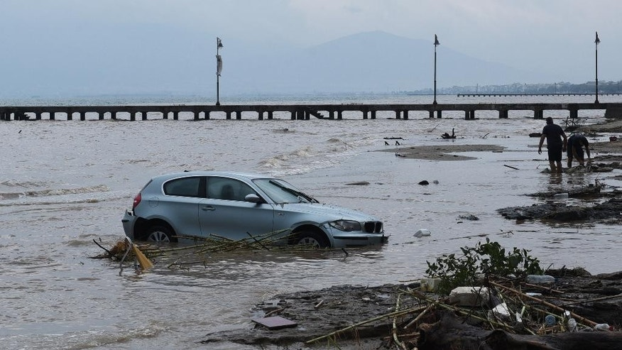 A car is abandoned in the sea in Agia Triada village about 20 kilometers from the city of Thessaloniki, northern Greece, after heavy overnight rain on Wednesday, Sept. 7, 2016. Greek authorities said three people are dead and one is missing after the floods, which damaged homes and businesses in the southern Peloponnese region _ where the deaths were recorded _ and near Thessaloniki. (AP Photo/Giannis Papanikos)