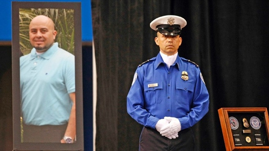 FILE - In this Nov. 12, 2013 file photo, a Transportation Security Administration officer stands in front of a portrait of slain TSA officer Gerardo Hernandez during his public memorial at the Los Angeles Sports Arena. A shooter who gunned down airport screening officers three years ago at Los Angeles International Airport in a terrifying attack that sent frantic passengers running for their lives is scheduled to plead guilty Tuesday, Sept. 6, 2016, to murder and other counts. Paul Ciancia agreed last week to plead guilty to all 11 charges in the rampage that killed one officer and wounded two others and a teacher who was headed for a flight. (Al Seib/Los Angeles Times via AP, Pool, File)
