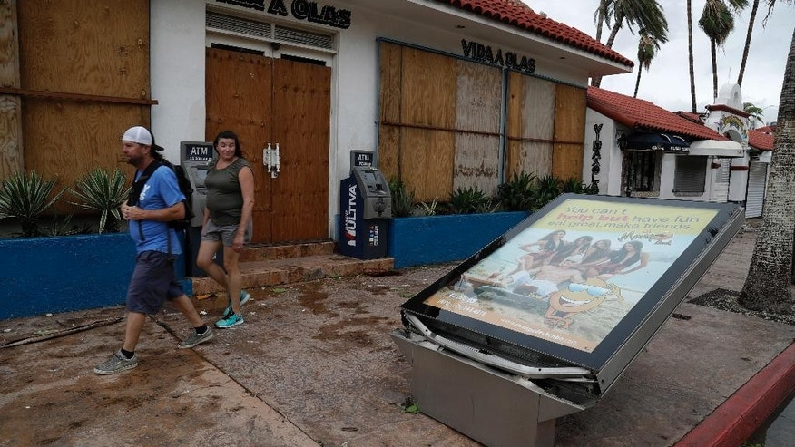 A couple walks next to an advertisement toppled by Hurricane Newton in Cabo San Lucas, Mexico, Tuesday Sept. 6, 2016. Hurricane Newton shattered windows, downed trees and knocked out power in parts of the twin resorts of Los Cabos on Tuesday, but residents were spared the kind of extensive damage seen two years ago when they were walloped by a monster storm. (AP Photo/Eduardo Verdugo)