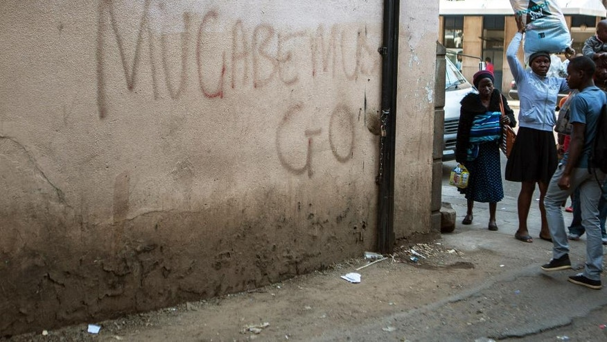 In this Tuesday, Sept, 6, 2016 photo, pedestrians walk near to a wall with anti Mugabe graffiti. For some in Zimbabwe enough is enough. The words are spelled out in anti government graffiti in the capital, one of several declarations of defiance that authorities have trouble scrubbing away. A two-week protest ban is currently in effect, but opposition groups plan another demonstration on Sept. 16 after it expires.  (AP Photo/Tsvangirayi Mukwazhi)