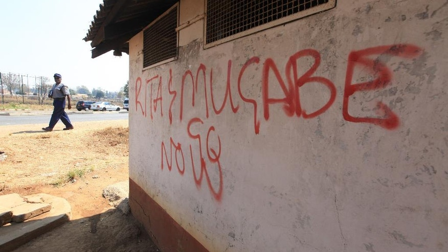 A policeman walks past a wall with anti Mugabe graffiti in this Monday, Sept, 5, 2016 photo. For some in Zimbabwe enough is enough. The words are spelled out in anti government graffiti in the capital, one of several declarations of defiance that authorities have trouble scrubbing away. The Southern African country is currently under a a two week protest ban by the government but opposition parties plan another demonstration on Sept. 16 after it expires. (AP Photo/Tsvangirayi Mukwazhi)