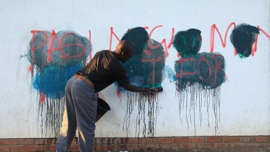 In this Tuesday, Sept. 6, 2016 photo, a caretaker of a building attempts to rub off anti government graffiti, in the capital Harare. For some in Zimbabwe enough is enough. The words are spelled out in anti government graffiti in the capital, one of several declarations of defiance that authorities have trouble scrubbing away. A two-week protest ban is currently in effect, but opposition groups plan another demonstration on Sept. 16 after it expires.  (AP Photo/Tsvangirayi Mukwazhi)