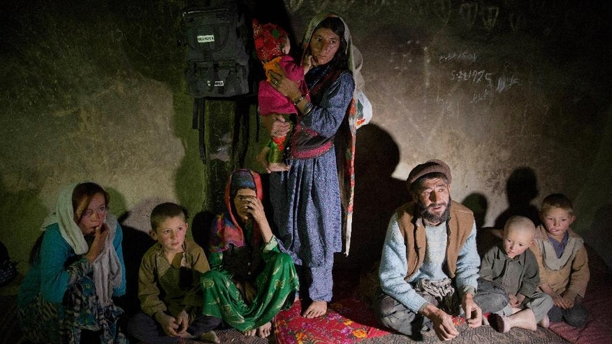 In this Aug. 18, 2016 photo, Saeed Beg, third right, and his family sit in their home during an interview with The Associated Press, in Sarkand village, Wakhan district of Badakhshan province, far northeastern Afghanistan. Beg and his family live in a two-room mud house with no electricity or running water, no bathroom, no kitchen and no furniture apart from a few threadbare rugs and a couple of thin mattresses. Beg describes how he exchanges his sheep and goats for food -- rice, cooking oil, salt-- in the barter system that is the main form of financial transaction here in the shadow of the Hindu Kush. (AP Photos/Massoud Hossaini)