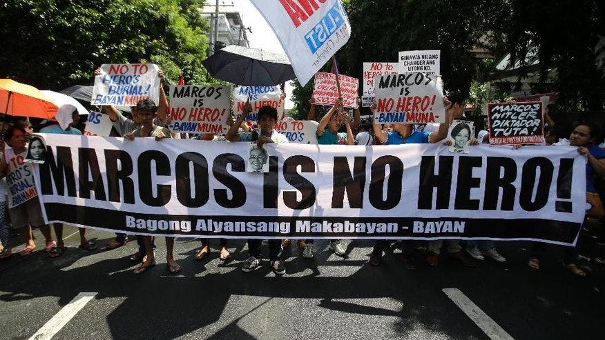 Anti-Marcos protesters holds slogans in a rally outside the Philippine Supreme Court in Manila, Philippines to coincide with the oral arguments following petitions filed by various civil society groups opposing the hero's burial of the late strongman Ferdinand Marcos at the Heroes Cemetery on Wednesday, Sept. 7, 2016. Lawyers for the Philippine government and heirs of Marcos said Wednesday the late dictator is qualified to be buried at a heroes' cemetery as a former president and war veteran despite opposition from his regime's human rights victims. (AP Photo/Aaron Favila)