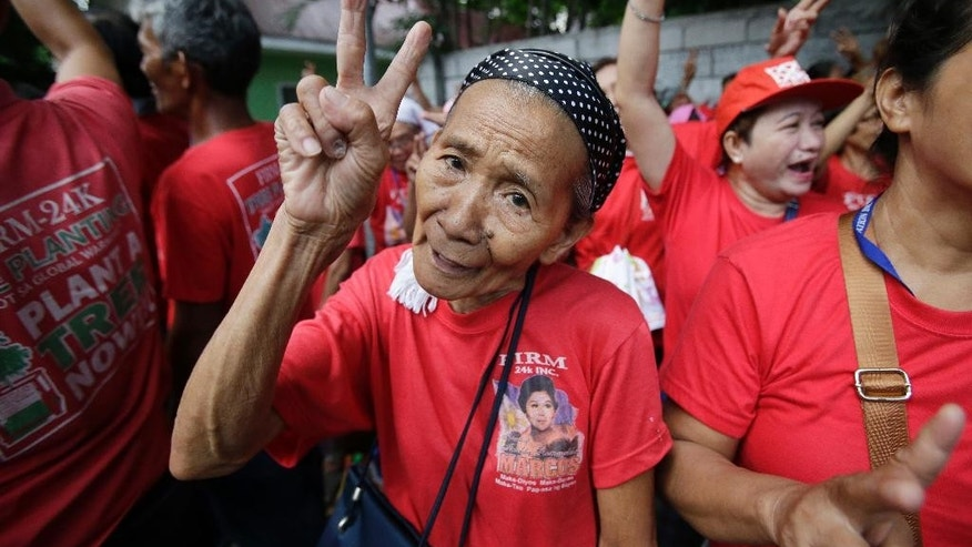 "Supporters of the late strongman Ferdinand Marcos flashes the ""V"" sign for victory near their anti-Marcos counterparts as they hold a rally outside the Philippine Supreme Court in Manila, Philippines to coincide with the oral arguments following petitions filed by various civil society groups opposing the hero's burial of Marcos at the Heroes Cemetery on Wednesday, Sept. 7, 2016. Lawyers for the Philippine government and heirs of Ferdinand Marcos said Wednesday the late dictator is qualified to be buried at a heroes' cemetery as a former president and war veteran despite opposition from his regime's human rights victims. (AP Photo/Aaron Favila)"
