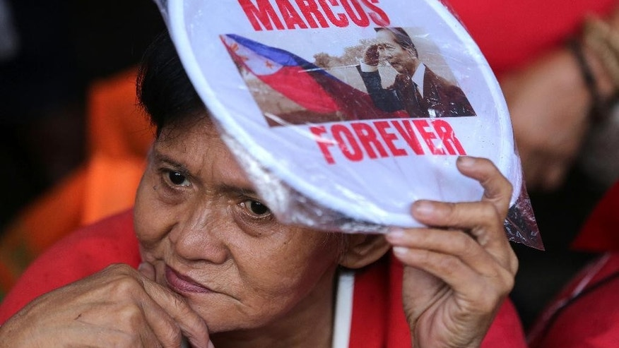 A supporter of the late strongman Ferdinand Marcos holds a fan near anti-Marcos counterparts as they hold a rally outside the Philippine Supreme Court in Manila, Philippines to coincide with the oral arguments following petitions filed by various civil society groups opposing the hero's burial of Marcos at the Heroes Cemetery on Wednesday, Sept. 7, 2016. Lawyers for the Philippine government and heirs of Ferdinand Marcos said Wednesday the late dictator is qualified to be buried at a heroes' cemetery as a former president and war veteran despite opposition from his regime's human rights victims. (AP Photo/Aaron Favila)