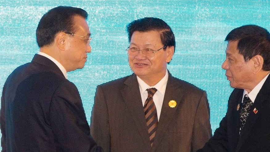 Chinese Premier Li Keqiang, left, shakes hands with President Rodrigo Duterte of the Philippines, right, as Laos' Prime Minister Thongloun Sisoulith looks on.