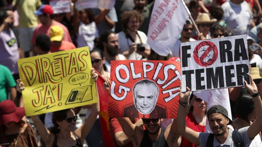 "Demonstrators hold up posters that read in Portuguese ""Direct elections now,"" left, ""Coup"", center, and ""Get out Temer,"" right, during a protest against Brazil's President Michel Temer after a military Independence Day parade in Brasilia, Brazil, Wednesday, Sept. 7, 2016. Brazil's former President Dilma Rousseff was removed from office for breaking fiscal responsibility laws in her management of the federal budget. Temer, once her vice president, will serve out her term which runs through 2018. (AP Photo/Eraldo Peres)"
