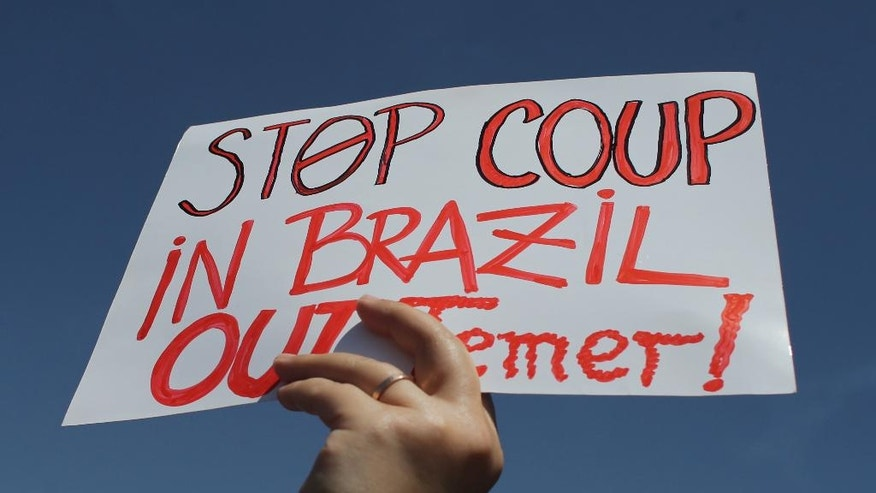 A demonstrator holds up a sign against Brazil's President Michel Temer after an Independence Day military parade in Brasilia, Brazil, Wednesday, Sept. 7, 2016. Brazil's former President Dilma Rousseff was removed for breaking fiscal responsibility laws in her management of the federal budget. Temer, once her vice president, will serve out her term which runs through 2018. (AP Photo/Eraldo Peres)