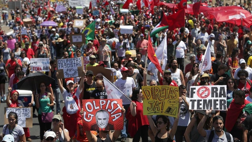 Demonstrators protest Brazil's President Michel Temer after an Independence Day military parade in Brasilia, Brazil, Wednesday, Sept. 7, 2016. Brazils' former President Dilma Rousseff was removed from office for breaking fiscal responsibility laws in her management of the federal budget. Temer, once her vice president, will serve out her term which runs through 2018. (AP Photo/Eraldo Peres)