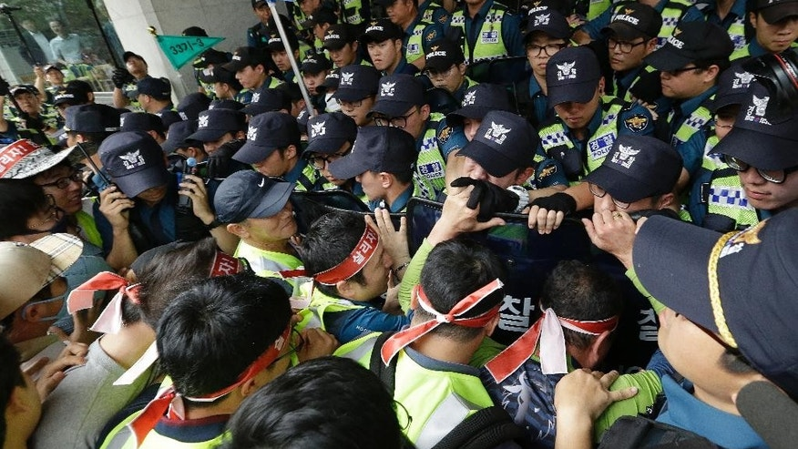 Workers from port-related organizations in Busan city scuffle with police officers during a rally to plead with the government and creditors of Hanjin Shipping Co. to map out measures to save the troubled shipper in front of the Hajin group Chairman Cho Yang-ho's office in Seoul, South Korea, Wednesday, Sept. 7, 2016. Hanjin Group said Tuesday it will inject $90 million, including $36 million from its chairman Cho's personal assets, to help resolve disruptions to container cargo transport caused by Hanjin Shipping Co.'s financial troubles. (AP Photo/Ahn Young-joon)