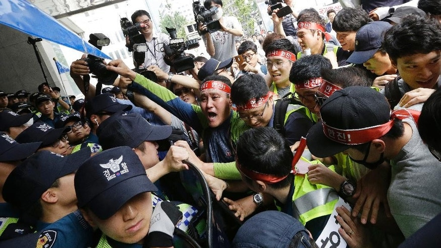 Workers from port-related organizations in Busan city scuffle with police officers during a rally to plead with the government and creditors of Hanjin Shipping Co. to map out measures to save the troubled shipper in front of the Hajin group Chairman Cho Yang-ho's office in Seoul, South Korea, Wednesday, Sept. 7, 2016. Hanjin Group said Tuesday it will inject $90 million, including $36 million from its chairman Cho's personal assets, to help resolve disruptions to container cargo transport caused by Hanjin Shipping's financial troubles. (AP Photo/Ahn Young-joon)
