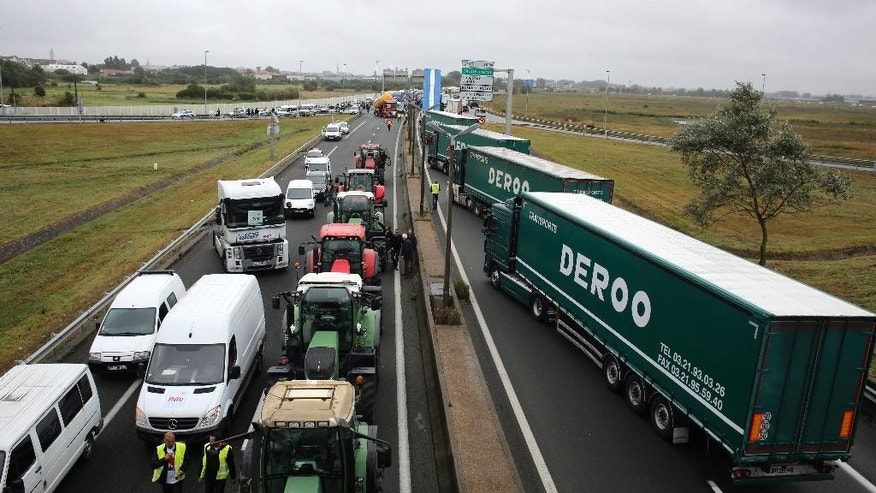 "Truckers and farmers block the highway near Calais, northern France, Monday Sept. 5, 2016. Hundreds of truckers in big rigs, farmers in tractors and dockers and merchants on foot blocked a major highway in northern France on Monday to demand the closure of the Calais migrant camp known as the ""jungle."" (AP Photo/Thibault Camus)"