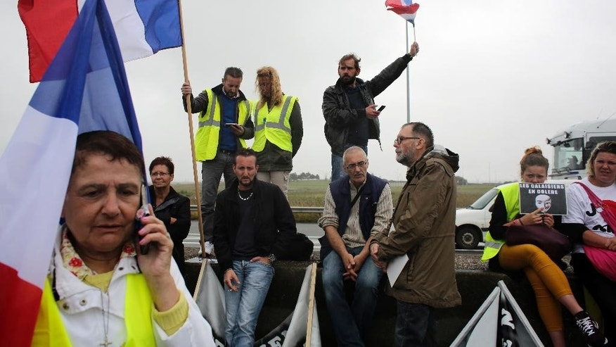 "Demonstrators hold French flags as truckers block the highway near Calais, northern France, Monday Sept. 5, 2016. Hundreds of truckers in big rigs, farmers in tractors and dockers and merchants on foot blocked a major highway in northern France on Monday to demand the closure of the Calais migrant camp known as the ""jungle."" (AP Photo/Thibault Camus)"