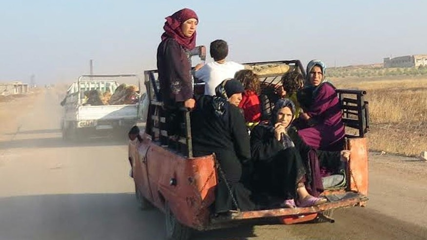 This photo provided by the Syria Press Center (SPC), an anti-government media group, shows civilians leaving the town of Suran, in Hama province, Syria, Thursday Sept. 1, 2016. Suspected government warplanes carried out several airstrikes in Syria's Hama on Thursday, killing at least 25 people, amid a lightning advance by insurgents on government-controlled areas of the central province. (Syria Press Center via AP)