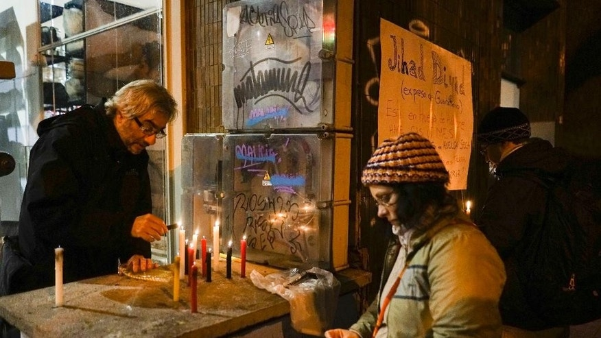 People light candles in the street near the place where former Guantanamo detainee Abu Wa'el Dhiab lives in Montevideo, Uruguay,Wednesday, Sept. 7, 2016. Uruguay's government says it is searching for another country to take Dhiab who is threatening to die on a hunger strike if he is not allowed to reunite with his family elsewhere. (AP Photo/Matilde Campodonico)