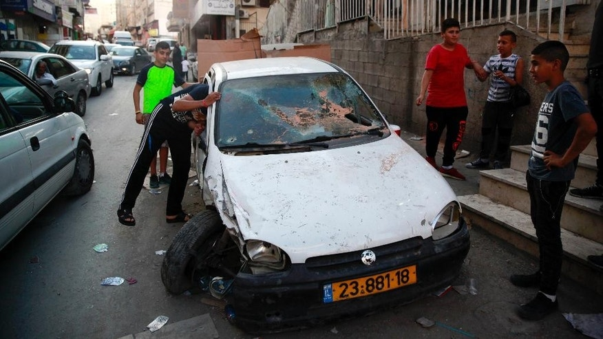 In this Monday Sept. 5, 2016 photo, Palestinian look at the car in which the driver was wounded and passenger killed by Israeli border police in Shuafat refugee camp in Jerusalem. Initially, police said the driver had tried to run over border police before they opened fire. But an amateur video on Tuesday appeared to show police shooting the car after it had been pulled over, suggesting it no longer posed a threat. Mustafa Nimr, a 27-year-old passenger, was fatally shot, while the driver was arrested. Police spokeswoman said Wednesday the driver Ali Nimr faces a series of charges, including death by negligence, drunk driving and driving without a license. (AP Photo/Mahmoud Illean)