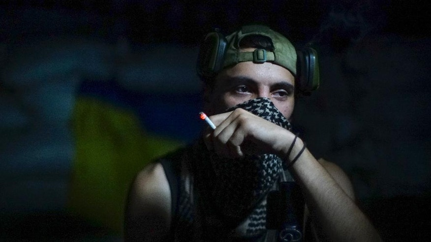 In this photo taken on Friday, Aug. 26, 2016, a Ukrainian soldier smokes in the village of Marinka, near Donetsk, eastern Ukraine. More than 9,500 people have been killed in the fighting that began in April 2014, according to United Nations figures, but despite the carnage or the weariness of those inflicting it, there's little expectation it will actually stop anytime soon. (AP Photo/Max Black)