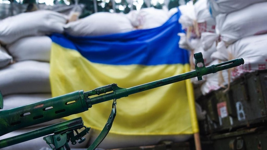 In this photo taken on Thursday, Aug. 25, 2016, a sniper rifle is placed in front of Ukrainian flag in the village of Marinka, near Donetsk, eastern Ukraine. More than 9,500 people have been killed in the fighting that began in April 2014, according to United Nations figures, but despite the carnage or the weariness of those inflicting it, there's little expectation it will actually stop anytime soon. (AP Photo/Max Black)