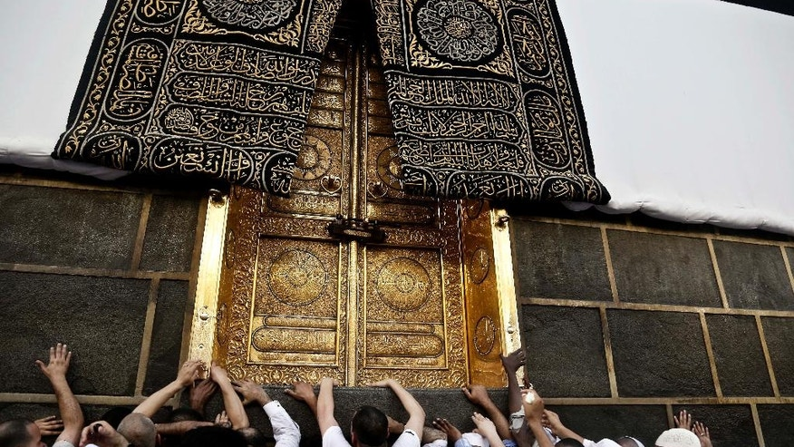 FILE -- In this Wednesday, Sept. 7, 2016 file photo, Muslim pilgrims touch the golden door of the Kaaba, Islam's holiest shrine, at the Grand Mosque in the Muslim holy city of Mecca, Saudi Arabia. Muslim pilgrims have begun arriving at the holiest sites in Islam ahead of the annual hajj pilgrimage in Saudi Arabia, with some weeping with their hands outstretched for a fleeting touch of the Kaaba. The cube-shaped shrine, at the center of Mecca's Grand Mosque, is the site the world's 1.6 billion Muslims pray toward five times a day. (AP Photo/Nariman El-Mofty, File)