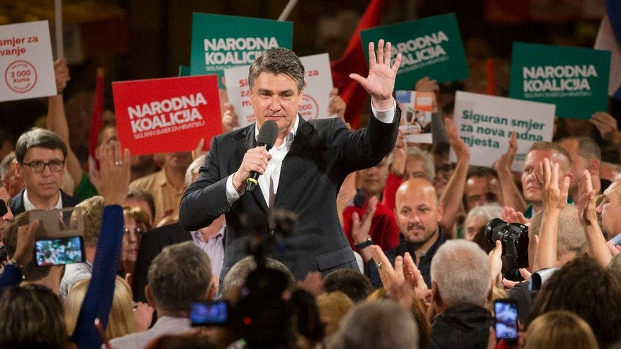 In this photo taken late Wednesday, Sept. 7, 2016, leader of the center-left coalition Zoran Milanovic greets supporters at a rally in Zagreb, Croatia. Croats go to the polls this weekend in a snap election that, despite the country's many problems, has been more about past divisions than future challenges facing the European Union's newest member state. (AP Photo/Darko Bandic)