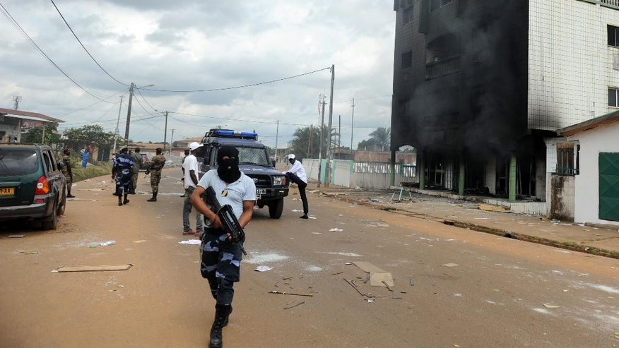 FILE - In this Thursday Sept. 1, 2016 file photo, Gabonese Police stand guard on a barricade following an election protest in Libreville, Gabon. Post election violence in Gabon has killed between 50 and 100 people, the opposition presidential candidate said Tuesday, Sept. 6, 2016, a toll much higher than the government's count of three in days of violent demonstrations against the president's re-election. ( AP Photo/Joel Bouopda, File)