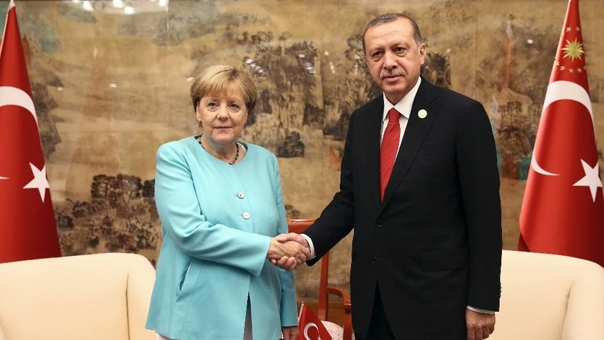 FILE - In this Sept. 4, 2016 file photo Turkish President Recep Tayyip Erdogan, right, and German Chancellor Angela Merkel pose for a photo before a bilateral meeting in Hangzhou in eastern China's Zhejiang province alongside the G20 Summit. (Kayhan Ozer/Pool Photo via AP, file)