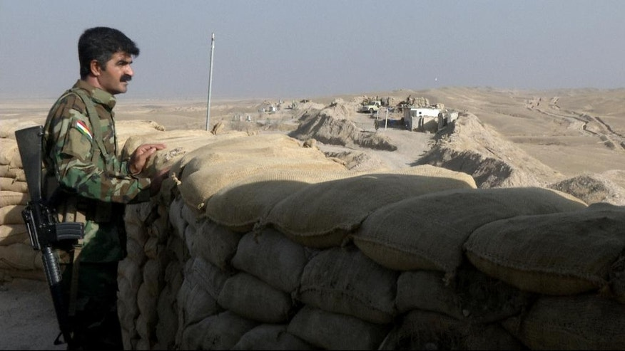 In this Monday, Sept. 5, 2016 photo made from video, a militiaman of the Kurdistan Freedom Party, an Iranian Kurdish opposition group, looks over the sandbags at a section of the frontline near the Iraqi city of Kirkuk. The leader of the armed Kurdish group in Iran says it received military weapons and explosives training from American and European advisers as part of the war against the Islamic State group. (AP Photo/Balint Szlanko)