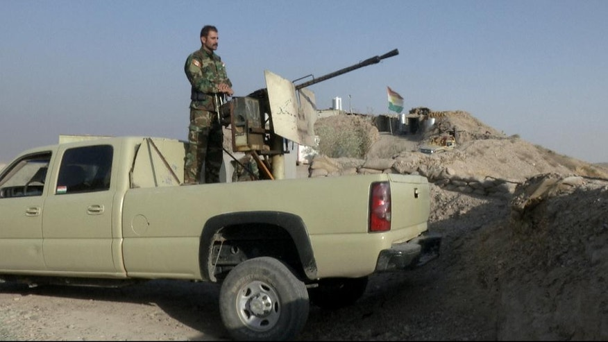 In this Monday, Sept. 5, 2016 photo, militiaman of the Kurdistan Freedom Party, an Iranian Kurdish opposition group, stands behind his truck-mounted machine gun on a section of the frontline near the Iraqi city of Kirkuk. The leader of the armed Kurdish group in Iran says it received military weapons and explosives training from American and European advisers as part of the war against the Islamic State group. (AP Photo/Balint Szlanko)