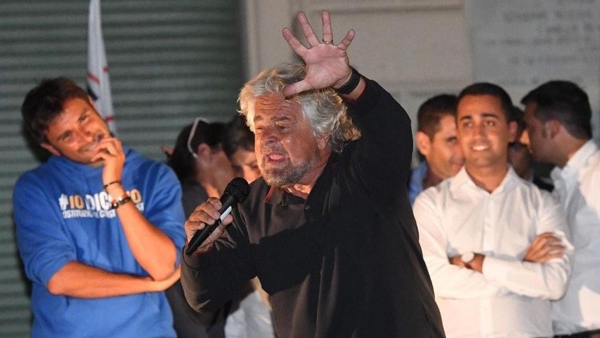 Leader of populist 5-Star Movement Beppe Grillo, center, speaks on stage at a rally in Nettuno, near Rome, Wednesday, Sept. 7, 2016. Grillo has given Rome's embattled mayor Virgina Raggi a public vote of confidence after her administration fell into disarray over a spate of resignations. (Alessandro Di Meo/ANSA via AP)