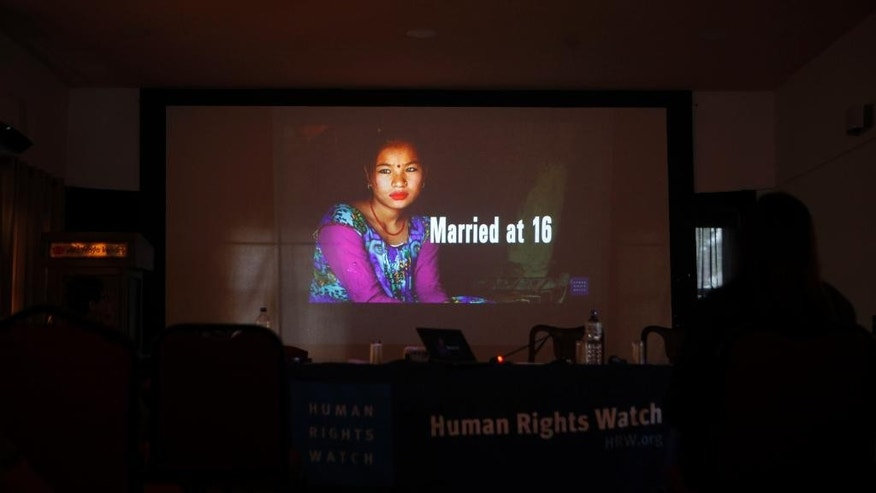 A portrait of a girl who got married at the age of 16 is shown in a presentation by New York-based Human Rights Watch during the release of a report on child marriage in Nepal in Kathmandu, Nepal, Thursday, Sept. 8, 2016. Traditional practices, poverty, last year's massive earthquake and Nepal's ongoing political instability mean child marriages remain a serious problem in the country, where 10 percent of the girls marry before they are 15, even though the government says it is making progress to combat the problem, rights groups say. (AP Photo/Niranjan Shrestha)