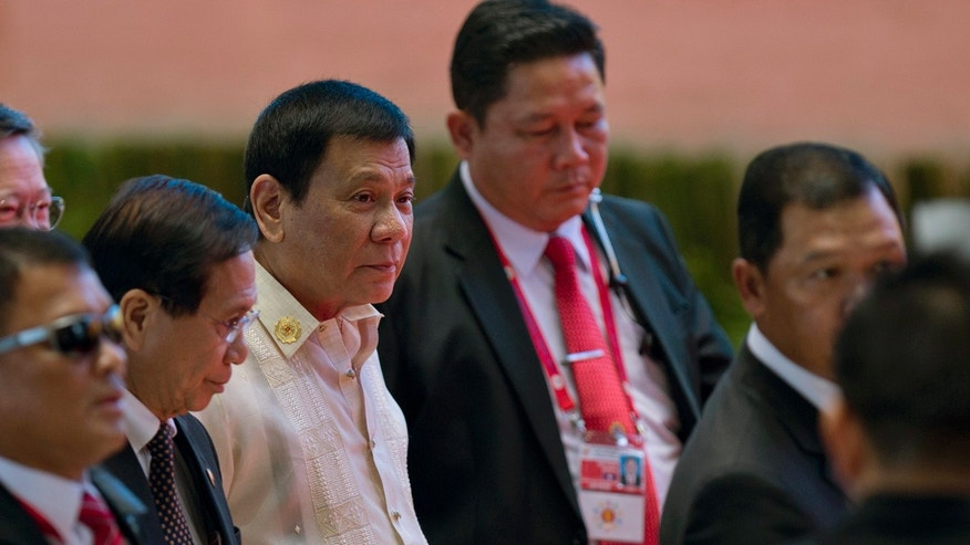 Philippine President Rodrigo Duterte, third left in white top, walks in with officials during ongoing 28th and 29th ASEAN Summits and other related summits at National Convention Center in Vientiane, Laos, Thursday, Sept. 8, 2016.