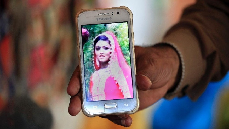 A local journalist shows the picture of slain British women Samia Shahid on a cell phone at his grocery store in Dina near Jhelum, in eastern Pakistan, Wednesday, Sept. 7, 2016. The Pakistani police are recommending that the ex-husband and the father of a British woman who was killed while on a family visit to Pakistan be tried on rape and murder charges according to a report shared exclusively with The Associated Press on Tuesday.  (AP Photo/Anjum Naveed)