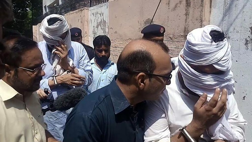 In this Monday, Sept. 5, 2016 photo, Pakistani police officers escort the detained father, second left face covered, and husband, right face covered, of slain British women Samia Shahid, to appear in court in Jhelum, in eastern Pakistan, Wednesday, Sept. 7, 2016. The Pakistani police are recommending that the ex-husband and the father of a British woman who was killed while on a family visit to Pakistan be tried on rape and murder charges according to a report shared exclusively with The Associated Press on Tuesday. (AP Photo/Malik Fida Hussain)