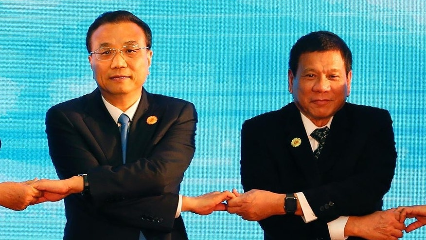 Chinese Premier Li Keqiang, left, and Philippine President Rodrigo Duterte link their hands during the ASEAN Plus Three summit in the ongoing 28th and 29th ASEAN Summits and other related summits at the National Convention Center Wednesday, Sept. 7, 2016 in Vientiane, Laos. (AP Photo/Bullit Marquez)