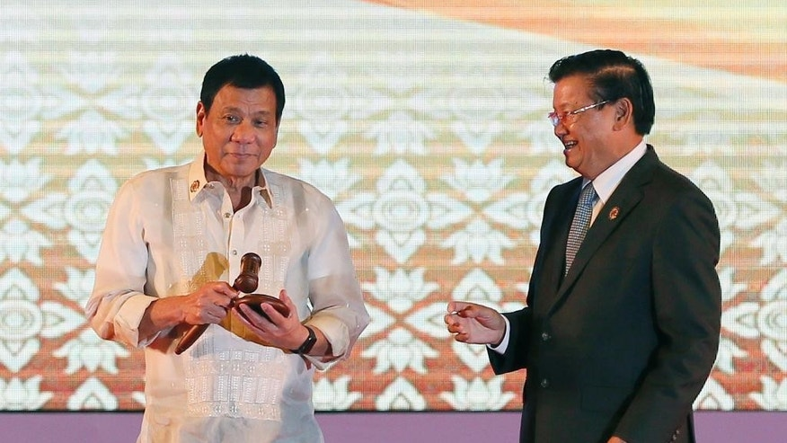 Philippine President Rodrigo Duterte, left, accepts the gavel to symbolize the handing over of ASEAN chairmanship to the Philippines from Laotian Prime Minister Thongloun Sisoulith at the conclusion of the 28th and 29th ASEAN Summits and other related summits at the National Convention Center Thursday, Sept. 8, 2016 in Vientiane, Laos. (AP Photo/Bullit Marquez)