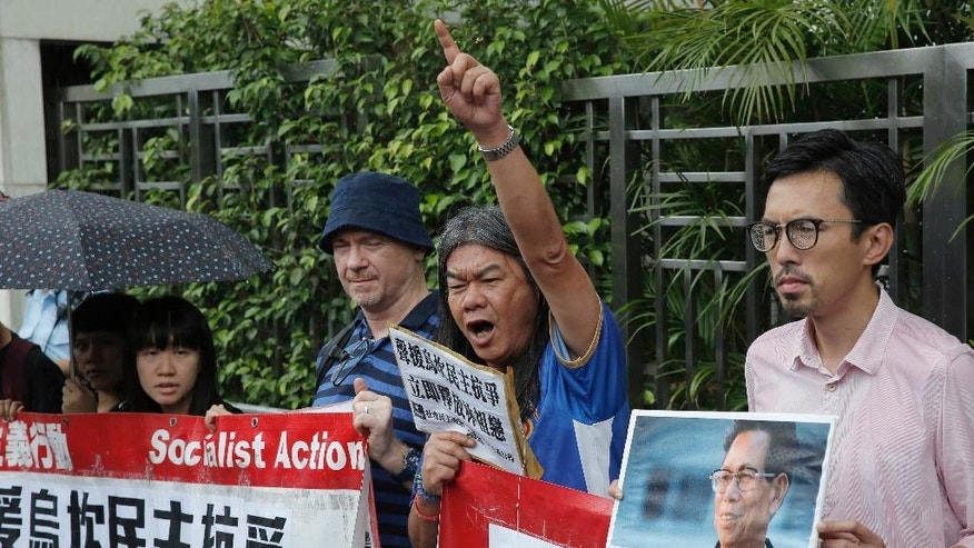 "Radical pro-democracy lawmaker Leung Kwok-hung, second from right, and other protesters holding a picture of Wukan village's leader Lin Zuluan during a demonstration outside the Chinese central government's liaison office in Hong kong, Friday, Sept. 9, 2016. The democratically elected mayor of the fishing village in southern China - which became the center of international attention five years ago for protests against land seizures - has been given three years in jail on bribery charges. The Chinese words on placard read: ""Release democratically elected secretary Lin Zuluan."" (AP Photo/Kin Cheung)"