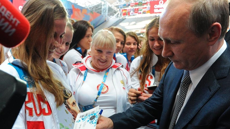 FILE- In this Friday, July 24, 2015 file photo, Russian President Vladimir Putin, right, signs autographs during his meeting with Russian athletes before the opening ceremony of the World Swimming Championships at the Kazan Arena stadium in Kazan, Russia. Donald Trump's statement that Russian President Vladimir Putin enjoys an 82 percent approval rating among his people wasn't hyperbole. Russia's two main polling agencies consistently give the man in the Kremlin ratings that would be the envy of Trump or his rival in the U.S. presidential election, Hillary Clinton. (Mikhail Klimentyev/RIA-Novosti, Kremlin Pool Photo via AP, File)