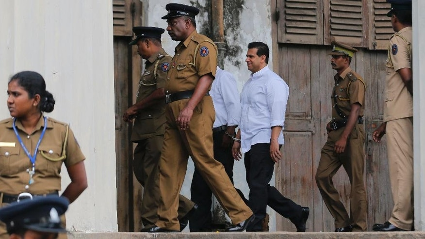 Sri Lankan police and prison officers escort former lawmaker Duminda Silva after he was sentenced to death, at a court complex in Colombo, Sri Lanka, Thursday, Sept. 8, 2016. A Sri Lankan court has sentenced Silva to death over the killing of a rival politician Bharatha Lakshman Premachandra in an election-related attack five years ago. Silva is likely to serve a life sentence because Sri Lanka has a moratorium on death penalty. (AP Photo/Eranga Jayawardena)