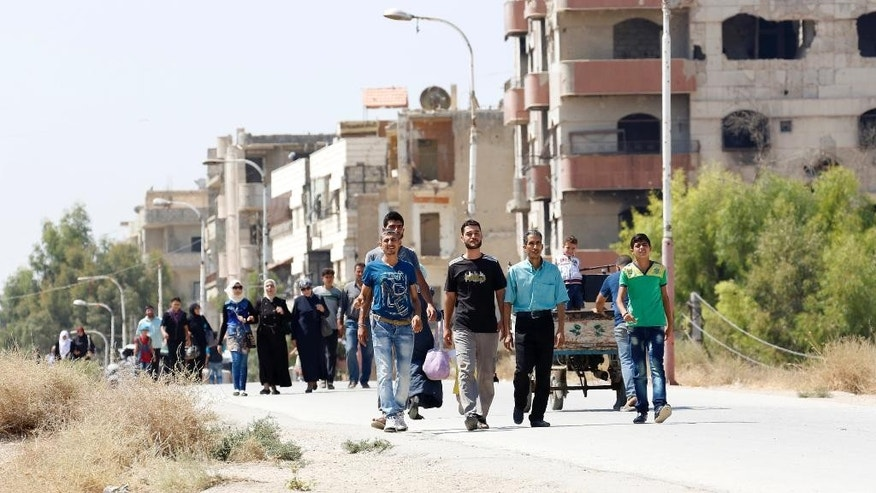 Residents of the Damascus suburb of Daraya leave the Moadamiyeh area on Thursday, Sept. 8, 2016. The second phase of an agreement reached by the Syrian government for people to leave Moadamiyeh was implemented Thursday, with nearly 150 people heading to a nearby suburb.(AP Photo)