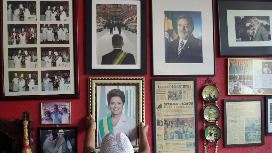 """In this Sept. 1, 2016 photo, Maria de Jesus Oliveira da Costa, known as """"Tia Zelia,"""" takes down an autographed photo given to her by Brazil's impeached President Dilma Rousseff, to show it to journalists at her restaurant in Brasilia, Brazil, where photos of former President Luiz Inacio Lula da Silva also hang. Costa would sometimes serve Lula and government ministers specialties like goat stomach stew at her hole-in-the-wall restaurant. Regarding Rousseff, she said: """"Unfortunately, she never ate what I cooked because she was always on a diet."""" (AP Photo/Eraldo Peres)"""