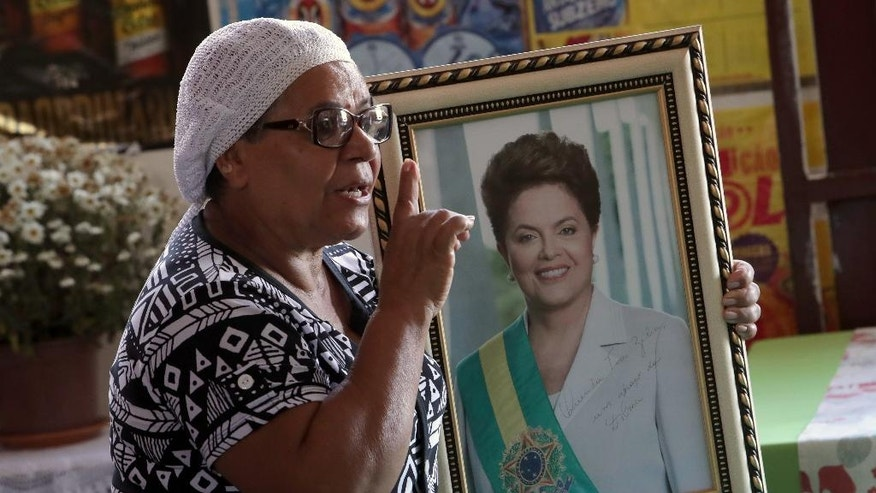 """In this Sept. 1, 2016 photo, Maria de Jesus Oliveira da Costa, also known as """"Tia Zelia,"""" shows an autographed portrait given to her by Brazil's impeached President Dilma Rousseff at her restaurant in Brasilia, Brazil. Costa says she began losing faith in the future when Rousseff, the long-time mentee and former chief of staff of Luiz Inacio Lula da Silva, succeeded him in 2011. Unlike the very charismatic Silva, Rousseff was never able to connect with average Brazilians, a situation made worse by a major recession and several scandals. (AP Photo/Eraldo Peres)"""